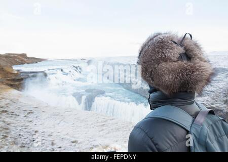Woman taking in view, Gullfoss Waterfall, located in the canyon of Hvita River in South West Iceland - Stock Photo