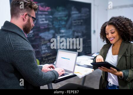 Colleagues in workplace using digital tablet and laptop smiling - Stock Photo
