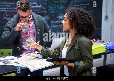 Colleagues in brewery office sampling beer from beer glasses - Stock Photo