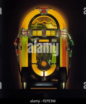 Illuminated vintage jukebox with attached gas pump nozzles - Stock Photo