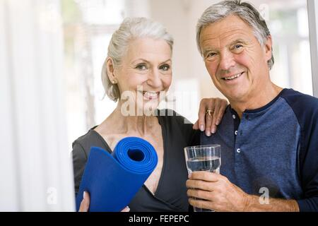Senior man and woman holding yoga mat and tumbler of water looking at camera smiling - Stock Photo