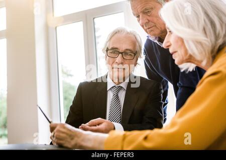 Senior adults in business meeting discussing paperwork - Stock Photo