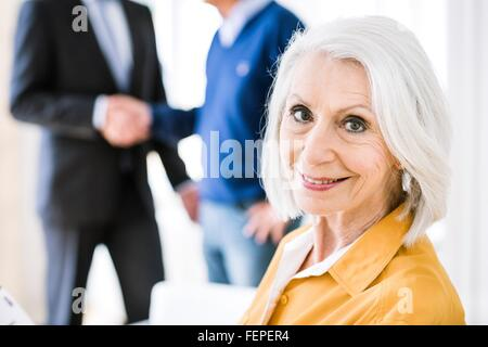 Senior woman in business meeting looking over shoulder at camera smiling - Stock Photo