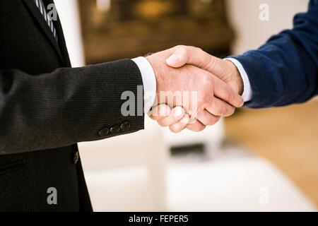 Cropped view of senior men shaking hands - Stock Photo