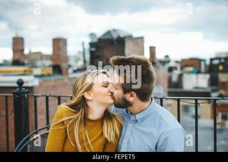 Romantic young couple kissing on city rooftop terrace - Stock Photo