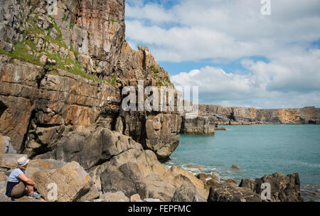 Female tourist admiring the dramatic cliffs along the Pembrokeshire coastline in South Wales - Stock Photo