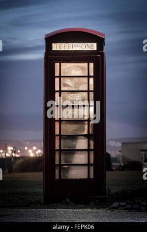 Man making call from red telephone box at night. UK - Stock Photo