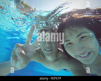 Smiling Man With Woman Showing Peace Sign While Swimming In Pool - Stock Photo