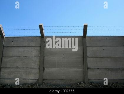 Low Angle View Of Barbed Wire On Fence Against Blue Sky - Stock Photo