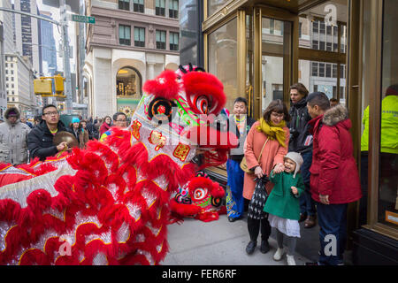 A dragon dancing troupe performs outside a Coach store in New York on Saturday, February 6, 2016 in advance of Monday's - Stock Photo