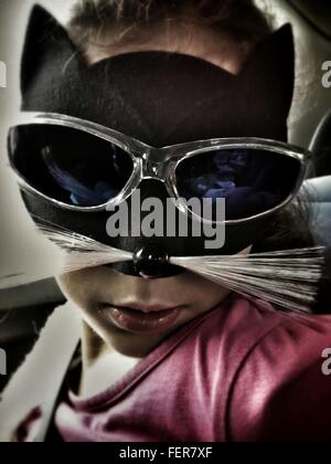 Close-Up Of Girl Wearing Cat Mask In Car - Stock Photo
