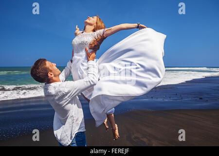 Happy newlywed family has fun on honeymoon holidays on sea black sand beach - married loving man tossing up high - Stock Photo