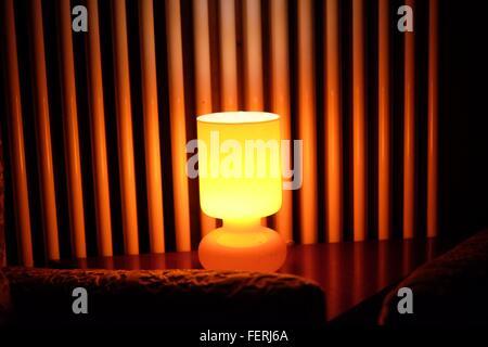 Illuminated Lamp On Table Against Wall - Stock Photo