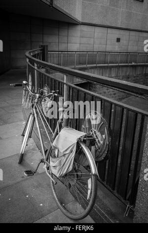 Bicycle Parked By Railing On Footpath - Stock Photo
