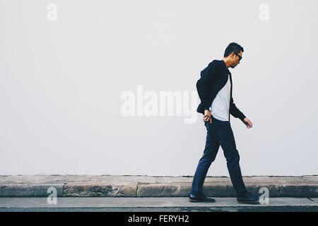 Young Man Walking On Street Against White Wall - Stock Photo