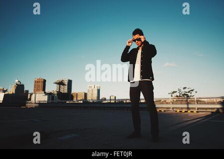 Low Angle View Of Man Wearing Sunglasses Against Clear Sky - Stock Photo