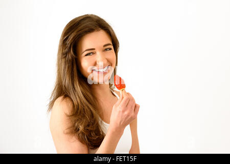 Young woman in sports top with strawberry smiling towards camera - Stock Photo