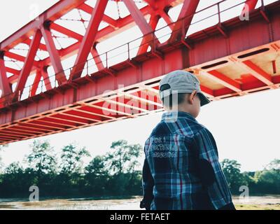 Rear View Of Boy Standing By Bridge Against Sky - Stock Photo