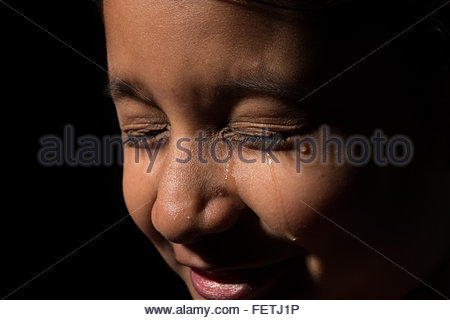 Young Asian child, could be a girl or boy crying with tears running down the face. - Stock Photo
