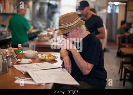 A man sits at the counter of The Cobble Hill Coffee Shop in Brooklyn, New York. - Stock Photo
