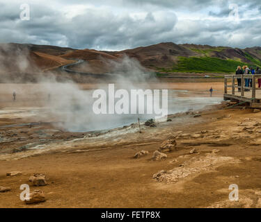 Northeast Iceland, Iceland. 1st Aug, 2015. Tourists on a viewing platform watch as steam and smoke from boiling - Stock Photo