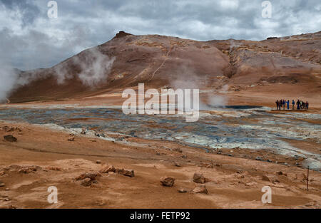 Northeast Iceland, Iceland. 1st Aug, 2015. Tourists watch as steam and smoke from boiling mud pools and steaming - Stock Photo