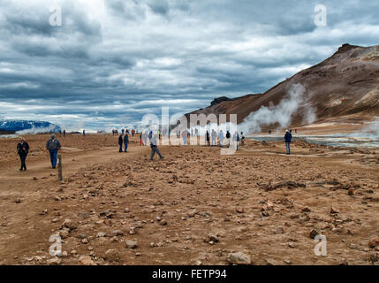 Northeast Iceland, Iceland. 1st Aug, 2015. Tourists walk as steam and smoke from boiling mud pools and steaming - Stock Photo