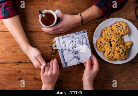 Mans and womans hands. Black-and-white photo. Couple. Tea and cookies. - Stock Photo