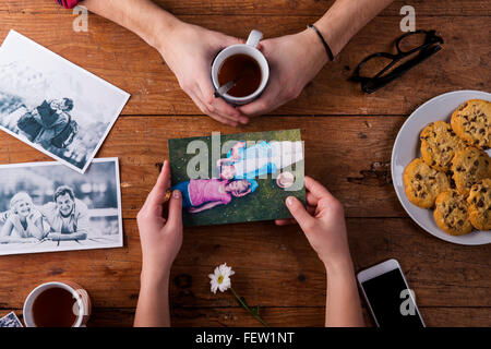 Mans and womans hands. Black-and-white photos. Couple. Tea, cookies, phone. - Stock Photo