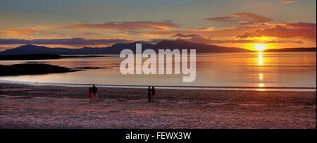 Sunset over Ganavan beach and a distant island of Mull, Argyll - Stock Photo