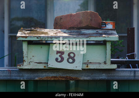 An old timber letter box sits on a fence held down by a  house brick, number 38 with peeling paint - Stock Photo