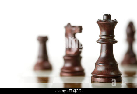 Horizontal image of a chess game with focus on the queen and a blurry pieces over white background, Copy space on - Stock Photo