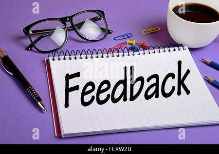 Feedback word written on notepad - Stock Photo