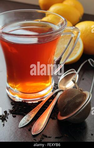 Cup of tea with lemon. Spoons and strainer on table - Stock Photo