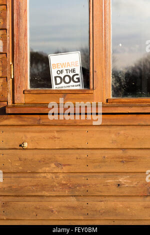 Beware of the dog please close the gate sign in window on brown shed - Stock Photo