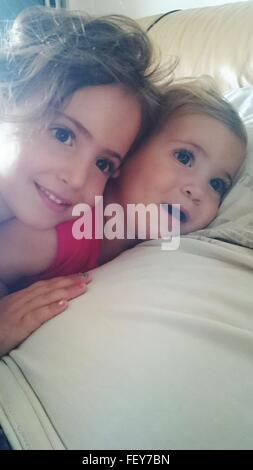 Siblings Relaxing On Bed At Home - Stock Photo
