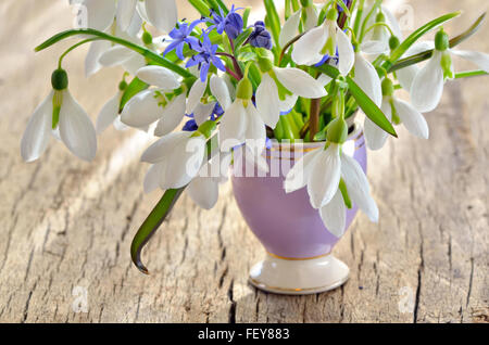 Bunch of Crocus and Snowdrops in a glass vase on old wooden table - Stock Photo