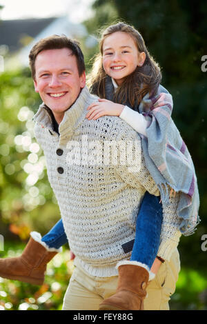 Father giving daughter piggyback - Stock Photo