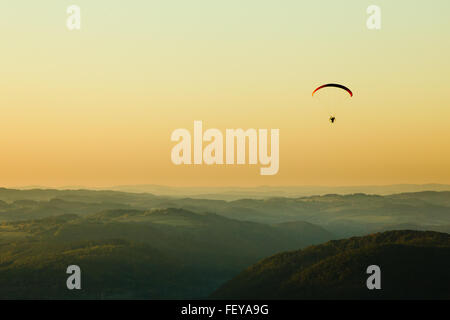 Moto paraglider above the landscape in sunset, copy space - Stock Photo