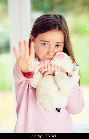 Girl sat alone holding hand out - Stock Photo