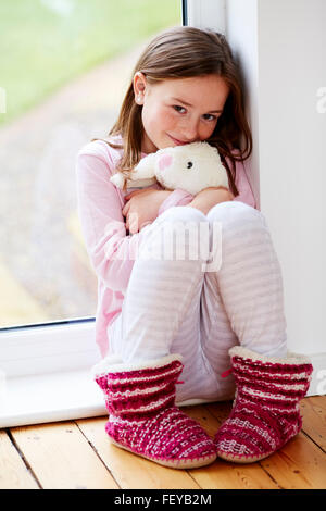 Little girl sat smiling - Stock Photo
