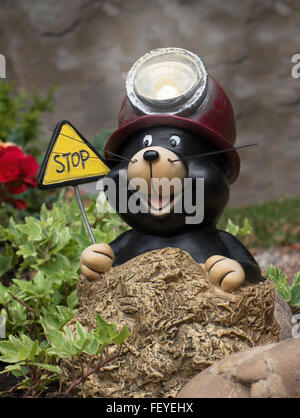 A funny, laughing mole figure with a helmet with miner's lamp and a sign STOP - Stock Photo