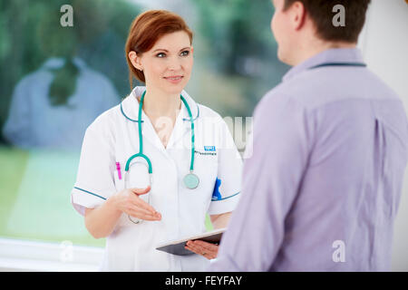 Doctor and nurse discussing notes - Stock Photo