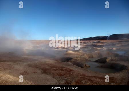 Steam Rising From Geyser At Salar De Uyuni Against Blue Sky - Stock Photo