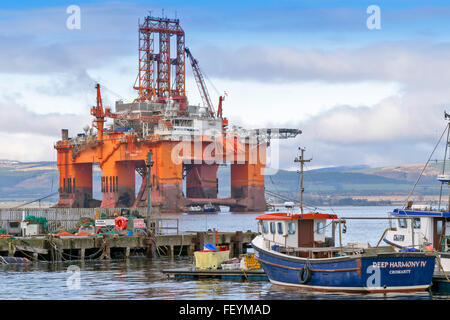 NORTH SEA OIL RIG WEST PHOENIX TOWERS OVER FISHING BOATS MOORED IN CROMARTY HARBOUR CROMARTY FIRTH SCOTLAND