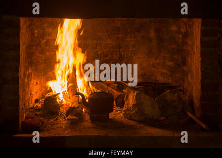 Traditional fireplace stove with fire burning and kettle. Winter time comfort concept. - Stock Photo