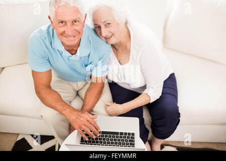 Smiling senior couple using laptop - Stock Photo