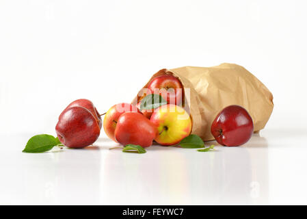 paper bag of ripe apples on white background - Stock Photo