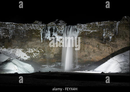 Seljalandsfoss Waterfall on the Golden Circle route lit up at night during winter in Iceland - Stock Photo