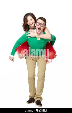 Happy couple piggybacking girl - Stock Photo